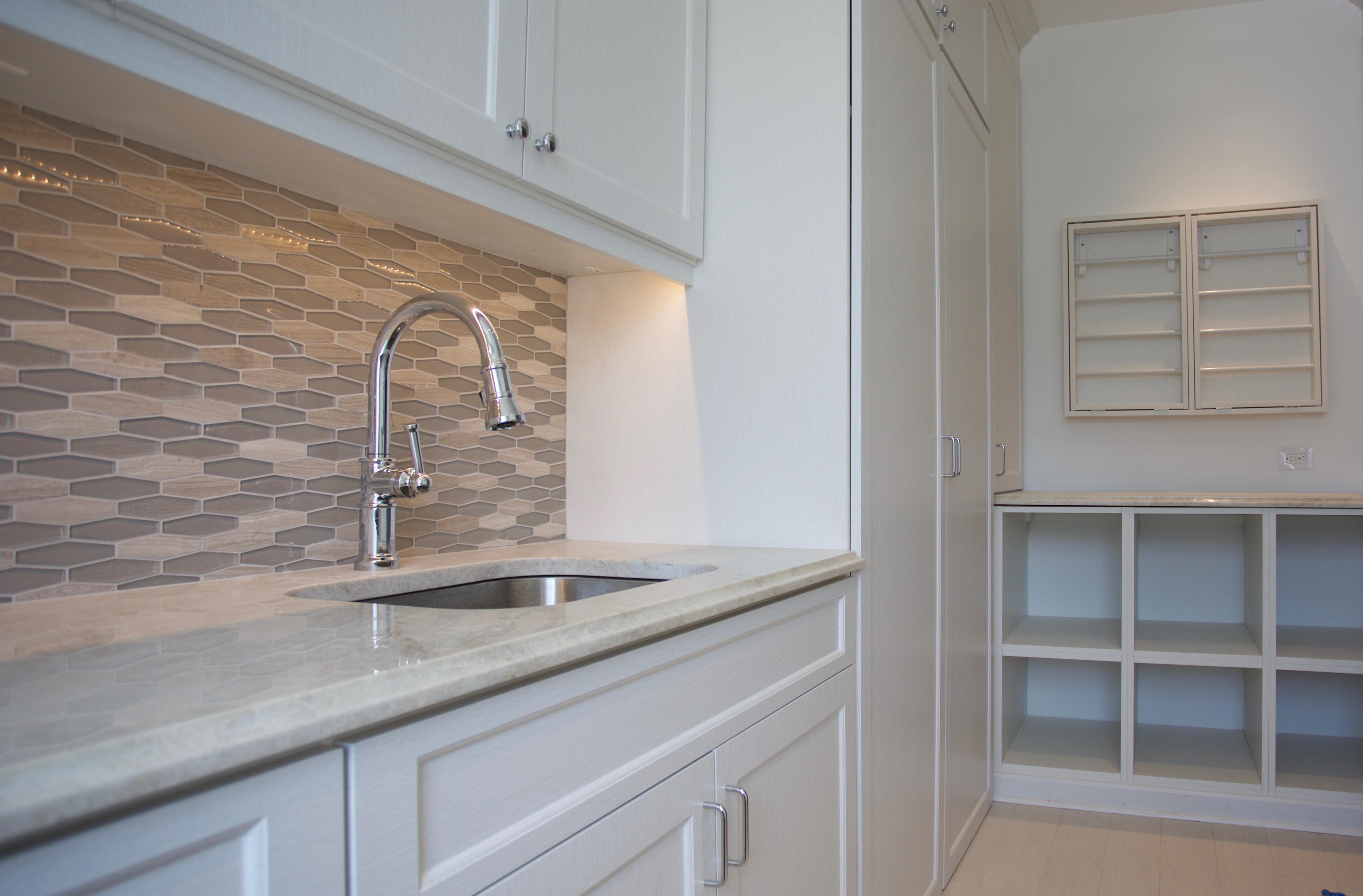 Latitude North Laundry with shaker style fronts, decorative base and crown moulding from Innovative Closet Designs
